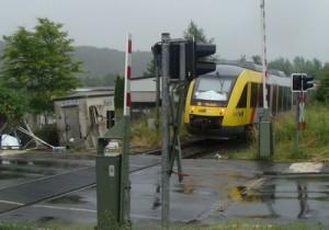 Ein Zug der Vogelsbergbahn auf dem Weg von Gießen nach Alsfeld passiert den Bahnübergang Edekastraße, es können keine Schranken geschlossen werden, es gibt kein Lichtsignal. Inzwischen sichern Bahnübergangssicherungsposten die Schienenquerung der Edekastraße.