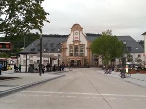 Das historische Bahnhofsgebäude in Marburg aus Richtung der Stadtmitte aus gesehen, davor die neuen Sägezahnanordnungen der Bushaltestellen für die Stadt- und Lokalbuslinien.