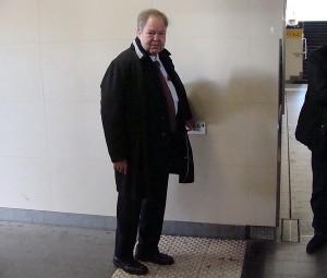 PRO BAHN-Ehrenvorsitzender Karl-Peter Naumann an einer der Hinweistafeln in Brailleschrift in der Unterführung des Marburger Bahnhofs.