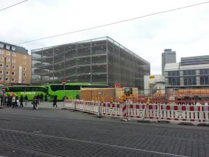 Links die markant-grünen Flixbusse, dahinter das neue Parkhaus. Rechts im Bild im Hintergrund das Hallendach des Hauptbahnhofs und davor die tiefe Baugrube des künftigen Hotels. Etwa in Höhe des weißen Containers wird künftig der Durchgang zwischen Bahn und Fernbus sein.
