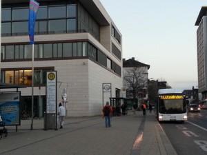 Die Stadtbuslinie 1 an der Haltestelle Berliner Platz in Gießen, direkt vor dem Rathaus mit der Glasfront des Stadtverordnetensitzungssaals im Vordergrund. Die Entscheidugnsträger blicken also auf den ÖPNV herab. Der Berliner Platz ist einer der zentralen Umsteigepunkte in Gießen.