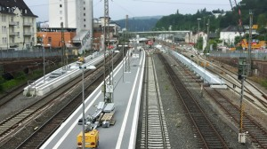 Die Bausphase im Bahnhof Siegen im Juli 2017. Es fährt kein Zug entgegen der Blickrichtung des Fotografen. Mittig des Bahnsteigs stehen die neuen Stützen der zukünftigen Fußgängerbrücke.